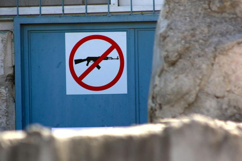 """No weapons"" sign on the door of a UNRWA building in Jerusalem. Photo: Kyle Taylor."