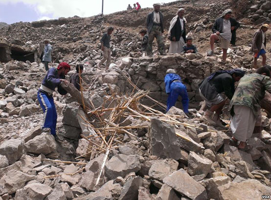 Locals help villagers that lost their homes recover their belongs that were scattered during the bombing of Hajar Aukaish, Yemen, April 2015. (VOA/A. Mojalli)